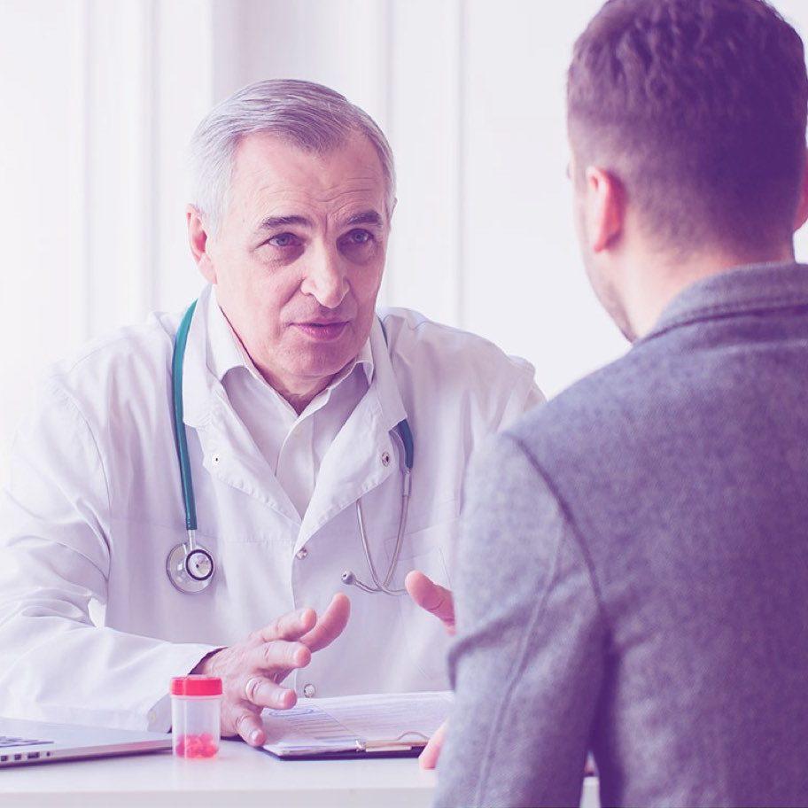 Arzt im persönlichen Gespräch mit einem Patienten, Krebsnachsorge