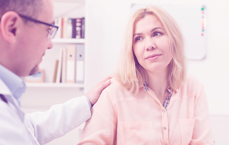Arzt legt im Gespräch seine Hand auf die Schulter einer Patientin