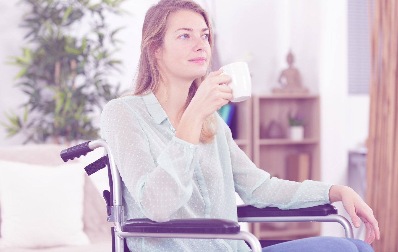 Eine junge Frau sitzt nachdenklich im Rollstuhl